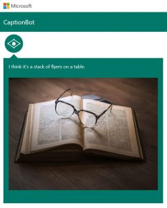 "Photo shows Captionbot.ai from Microsoft which has been shown a photo of a pair of glasses resting on an open book, which it believes is a ""stack of flyers on a table""."