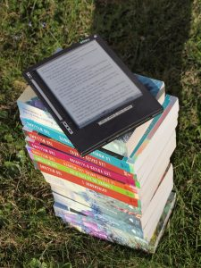 ereader placed on top of a pile of printed books
