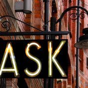 "Street sign with the word ""ASK"" lit up under a lamp"