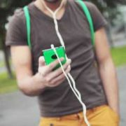 Teenage boy walking with handheld device with earphones attached. Image is just of his torse