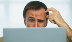 Man scratching his head in confusion at a computer screen