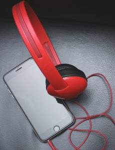 Space Gray Iphone 6 and Red On-ear Headphones