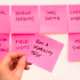 A collection of pink sticky notes being positioned on a board